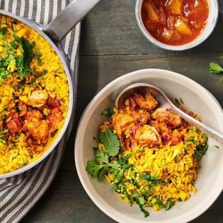Kruidige kip-biryani met gele rijst en koriander