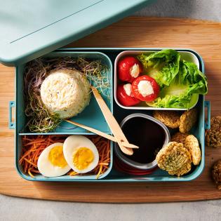 Oosterse bentobox met rijst, ei en sojadip